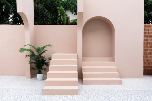 Minima scena di spazio vuoto con parete dipinta di rosa e piccolo gradino con arco