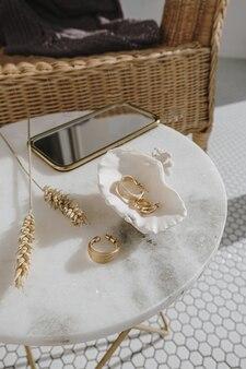 Composizione fashion minimal con orecchini dorati in conchiglia su tavola di marmo con specchio e gambi di grano