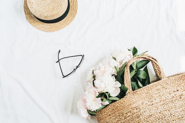 Superficie femminile minimale con cappello di paglia, occhiali, bouquet di fiori di peonia bianca in sacchetto