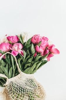 Minimal flat lay, vista dall'alto del bouquet di fiori di peonie bianche e rosa isolato su superficie bianca