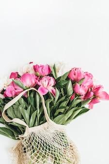 Laici minimalista, vista dall'alto del bouquet di fiori di peonie bianche e rosa sulla superficie bianca