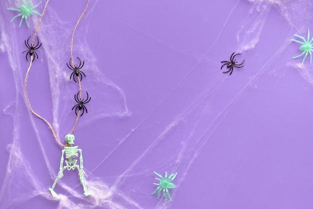 Sfondo di halloween minimo con scheletro appeso, ragnatela e linea di ragni neri su carta al neon viola vibrante. vista dall'alto, sfondo alla moda.