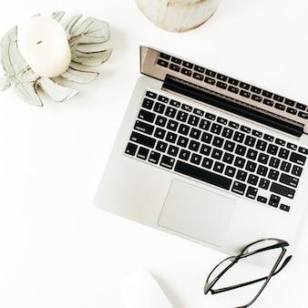 Area di lavoro minima home office scrivania con laptop, occhiali su bianco