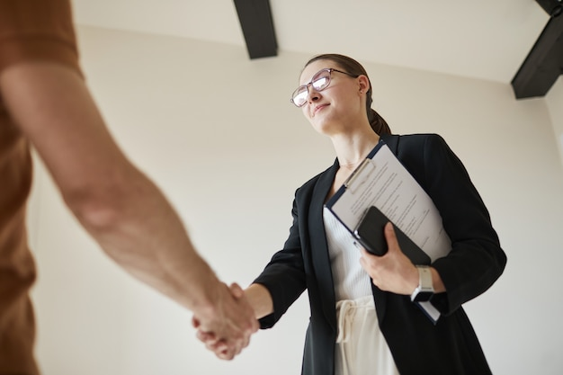 Ritratto minimo ad angolo basso di agente immobiliare femminile che stringe la mano al cliente, copia spazio