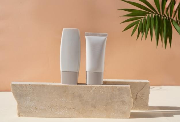 I prodotti cosmetici moderni minimali vengono visualizzati con due tubi su sfondo beige con sovrapposizione di ombre