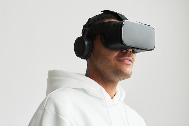 Ritratto minimo dell'uomo moderno che indossa l'auricolare vr su sfondo bianco, copia spazio