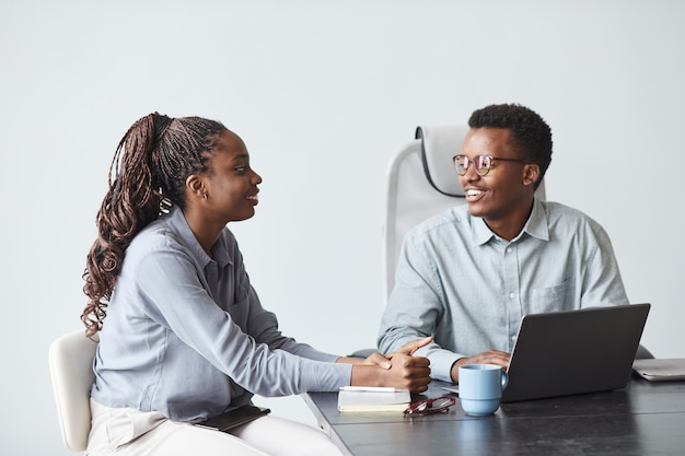 Ritratto minimo di due giovani colleghi afroamericani che collaborano al progetto e sorridono mentre usano il laptop insieme in ufficio, copia spazio