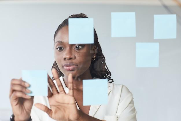 Ritratto minimo di giovane donna d'affari afro-americana che mette note adesive sulla parete di vetro mentre pianifica il progetto in ufficio, copia spazio