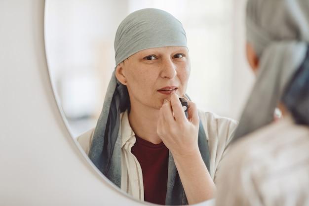 Ritratto di riflessione minima di donna calva matura che indossa trucco e rossetto mentre si guarda nello specchio a casa, abbracciando la bellezza, l'alopecia e la consapevolezza del cancro, lo spazio della copia