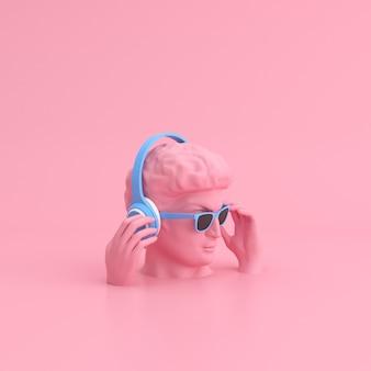 Scena minima di occhiali da sole e cuffie sulla scultura della testa umana.