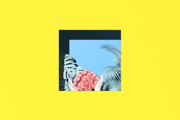 La scena minima di foglie tropicali e le mani tengono in mano una rosa con copia spazio a forma quadrata su sfondo giallo, foglia di palma e mostera. rendering 3d