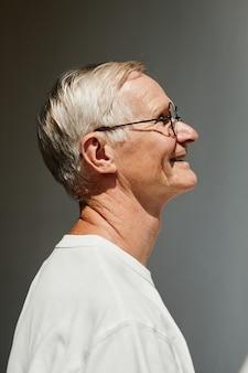 Ritratto minimo di vista laterale di un uomo anziano sorridente illuminato dalla luce del sole contro il muro grigio