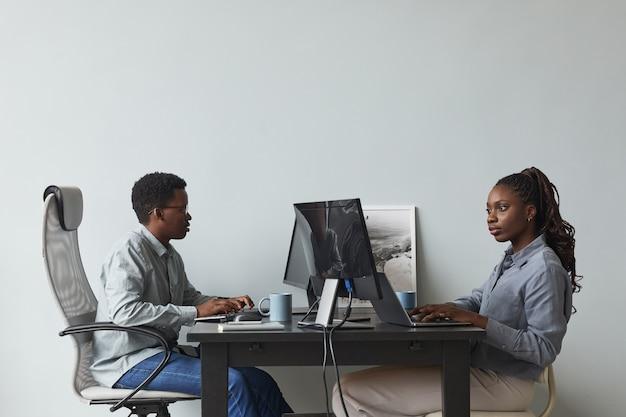 Ritratto con vista laterale minima di due giovani afro-americani che utilizzano computer e scrivono codice mentre lavorano nell'ufficio di sviluppo software, spazio di copia