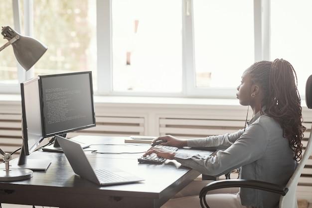 Ritratto minimo di vista laterale di giovane donna afro-americana che usa il computer e scrive codice mentre è seduto contro la finestra nell'ufficio di sviluppo software, copia spazio