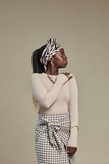 Ritratto minimo di vista laterale di giovane donna afroamericana che guarda lontano mentre indossa un accessorio etnico...