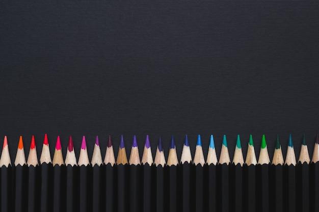Sfondo minimo di cancelleria. set di matite colorate disposte in linea su sfondo nero.