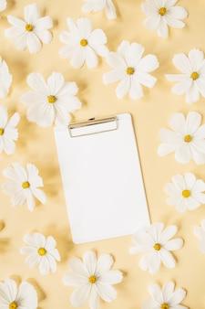 Concetto in stile minimale. ghirlanda di fiori di camomilla margherita bianca su giallo pallido con tavoletta bianca