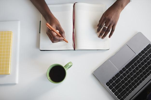 Vista dall'alto minima della donna afro-americana irriconoscibile che scrive nel pianificatore al posto di lavoro di affari bianco