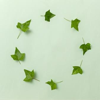 Invito alla ghirlanda di tendenza minimale con foglie di edera su sfondo verde. mockup contemporaneo con bordo e cornice per il testo.