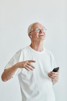Ritratto verticale minimo di un uomo anziano sorridente che balla e tiene in mano lo smartphone su sfondo bianco