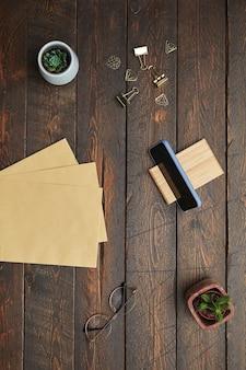 La minima vista sopra la disposizione piana di accessori per il business carta artigianale, bicchieri e piante grasse su sfondo di legno testurizzato sul posto di lavoro,