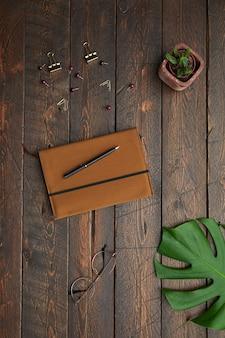 La minima vista sopra la disposizione piana di accessori per il business planner in pelle, occhiali e perni su sfondo di legno testurizzato sul posto di lavoro,