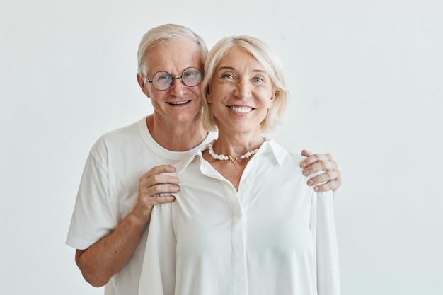 Minimo mezzo busto ritratto di una moderna coppia di anziani che si abbraccia su uno sfondo bianco e guarda ...