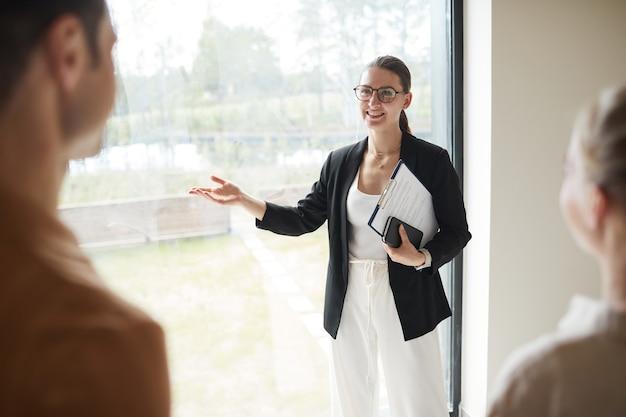 Ritratto minimo in vita di un agente immobiliare sorridente che fa un tour dell'appartamento alla coppia mentre si trova vicino alla finestra, copia spazio