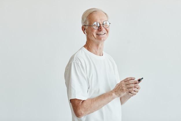 Ritratto minimo della vita in su dell'uomo anziano sorridente che tiene smartphone contro lo spazio bianco della copia del fondo