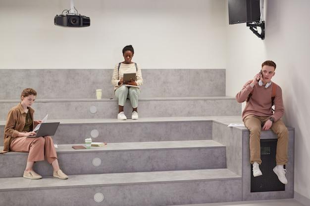 Minima ripresa grandangolare di diversi gruppi di studenti che si rilassano nella moderna lounge della scuola durante la pausa, copia spazio