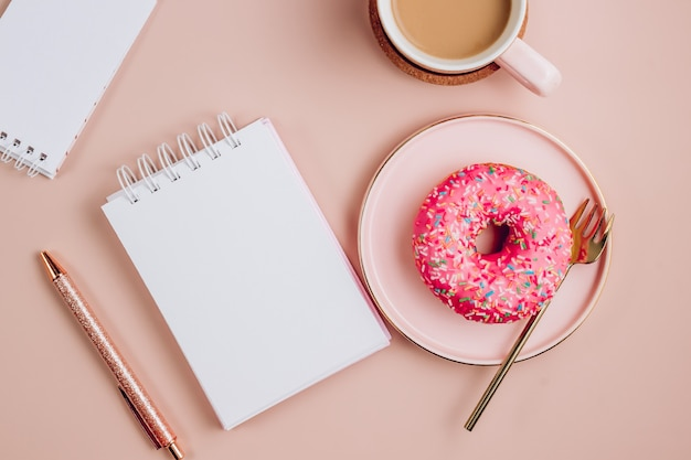 Posto di lavoro minimo con taccuino in bianco bianco, tazza di caffè e ciambella su sfondo rosa