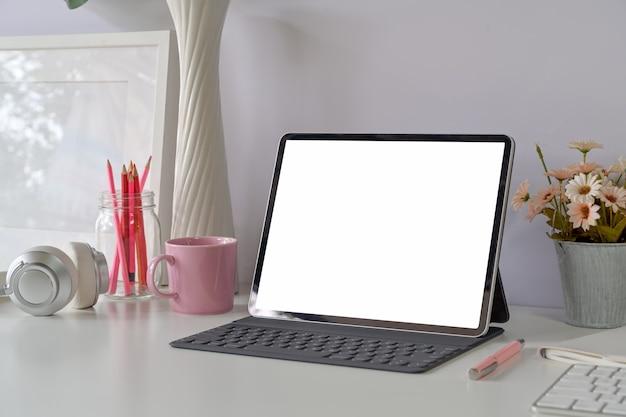 Spazio di lavoro minimo con tablet a schermo vuoto.