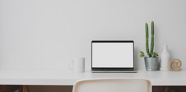 Area di lavoro minima con computer portatile aperto e decorazioni sulla tavola bianca e sulla parete bianca