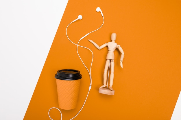 Concetto di minimalismo. bicchiere di carta e mock up uomo su sfondo arancione