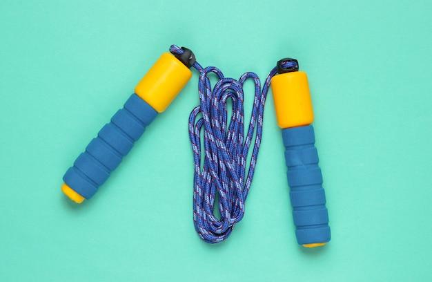 Il minimalismo concetto di fitness. saltare la corda su uno sfondo blu.