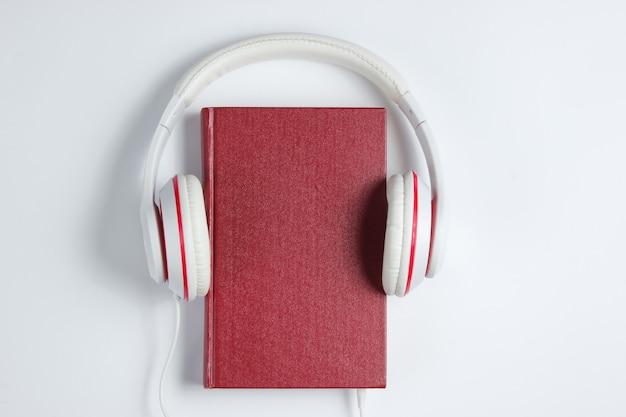 Il minimalismo online ascolta il concetto di libri. libro audiolibro con le cuffie su uno sfondo bianco. vista dall'alto