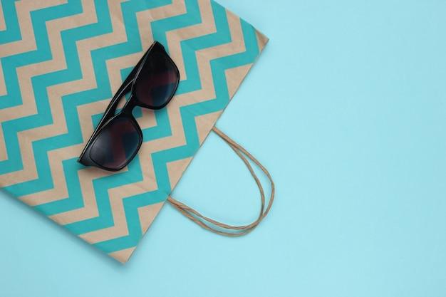 Concetto di acquisto minimalista. shopping bag di carta e occhiali da sole su sfondo blu.