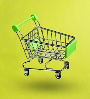 Concetto di acquisto minimalista. carrello della spesa giocattolo su sfondo verde. foto con ombra