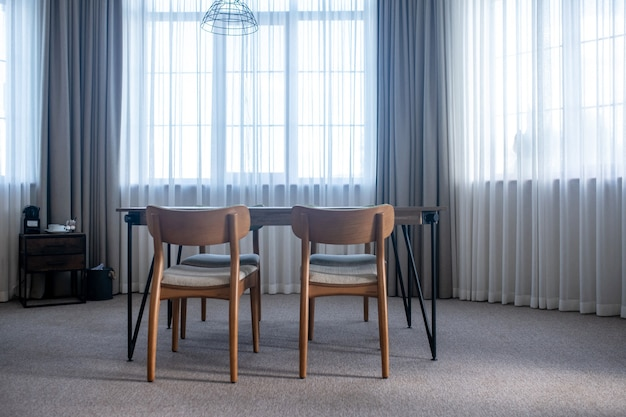 Minimalismo. tavolo con sedie su moquette al centro della stanza con ampie finestre con tende durante il giorno
