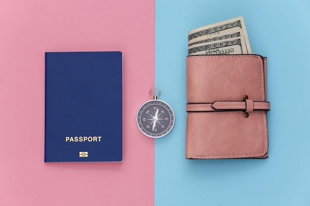 Viaggio minimalista, avventura piatta. borsa, passaporto e bussola su sfondo pastello blu-rosa. vista dall'alto