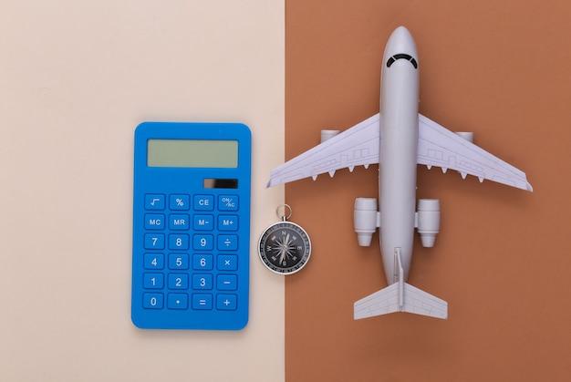 Il minimalismo viaggia piatto. bussola, calcolatrice e aereo su sfondo marrone beige. vista dall'alto