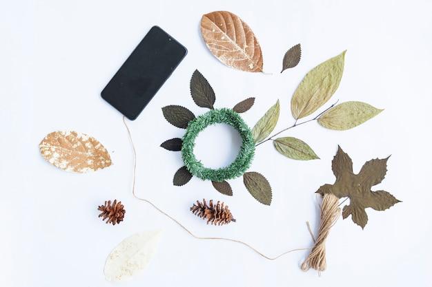 Concetto di autunno minimalista. foglie secche, fiori di pino, ghirlanda di krans, filato di tela da imballaggio, smartphone isolato su sfondo di carta bianca