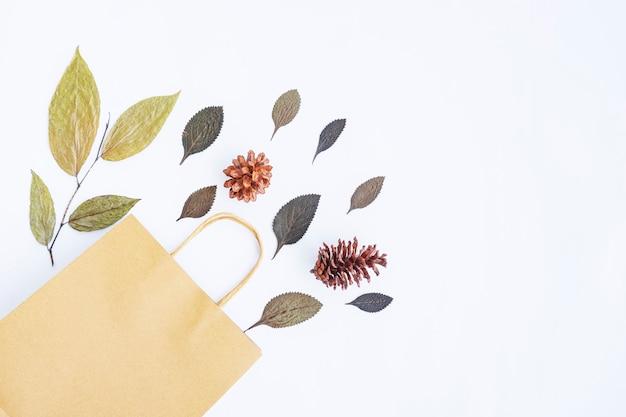 Concetto di autunno minimalista. foglie secche, fiori di pino, sacchetti di carta isolati su sfondo di carta bianca
