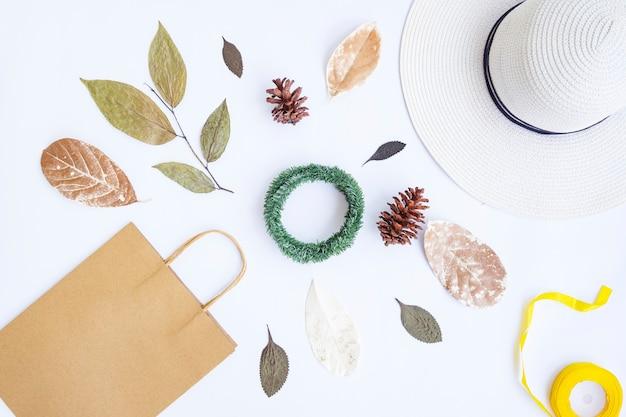 Concetto di autunno minimalista. sacchetto di carta, cappello bianco, corda del nastro, foglie secche, fiori di pino, corona di krans isolata su sfondo di carta bianca. concetto di natale minimalista