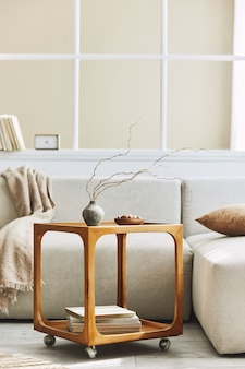 Composizione minimalista dell'interno del soggiorno con divano neutro, tavolino di design in legno, fiori secchi in vaso, cuscino, finestra, decorazione ed eleganti accessori personali nell'arredamento della casa.