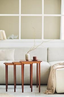 Composizione minimalista dell'interno del soggiorno con divano neutro, tavolino in legno di design, fiori secchi in vaso, cuscino, finestra, decorazione ed eleganti accessori personali