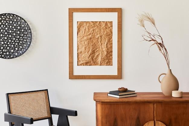 Composizione minimalista del soggiorno con cornice marrone finta, pianta, poltrona retrò, foglia tropicale essiccata, decorazione ed eleganti accessori personali in un elegante arredamento per la casa. modello.