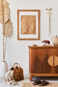 Composizione minimalista del soggiorno con cornice marrone, moquette, macramè, foglie tropicali essiccate, decorazioni ed eleganti accessori personali in un elegante arredamento per la casa.