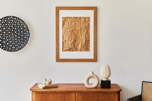 Composizione minimalista del soggiorno con cornice marrone, pianta, poltrona retrò, foglia tropicale essiccata, decorazione ed eleganti accessori personali in un elegante arredamento per la casa.
