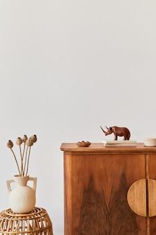 Composizione minimalista del soggiorno con copia spazio, pianta, poltrona retrò, foglia tropicale essiccata, decorazione ed eleganti accessori personali in un elegante arredamento per la casa.